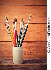 Vintage vertical retro photo of jar with paintbrushes