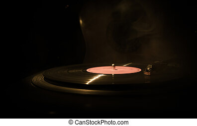Vintage vinyl record playing on player and acoustic guitar on background with fire orange smoke. Blues concept.