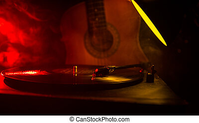 Vintage vinyl record playing on player and acoustic guitar on background with fire orange smoke. Blues concept. With Toy car