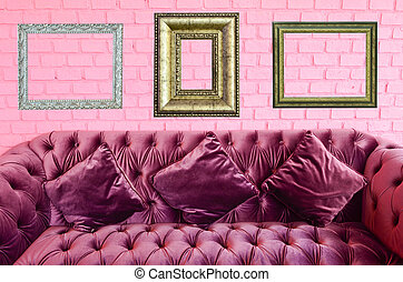 Vintage violet sofa and vintage picture frame on pink brick wall