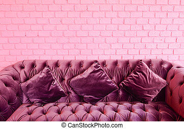 Vintage violet sofa with pink brick wall