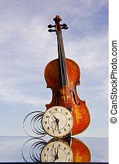 vintage violin with old clock on mirror