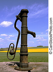 Old fashioned iron water pump and blue sky in the background
