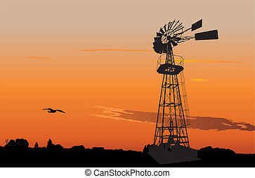 Vintage water pumping windmill - Silhouette of a vintage...