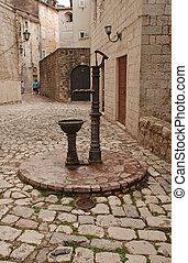 Vintage water well in a medieval town in Kotor, Montenegro