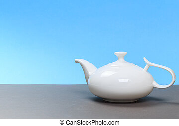 vintage white porcelain teapot on gray board and blue background