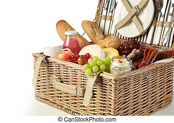Vintage wicker picnic hamper filled with food