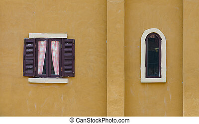 Vintage window on yellow cement wall