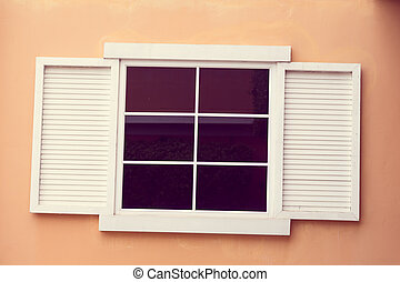 Vintage window on yellow cement
