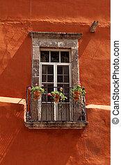 Vintage window with balcony on orange wall