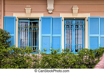 Vintage windows with blue shutters in old house, Provence, France