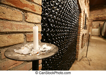 Vintage wine bottles stacked in the old cellar of the winery