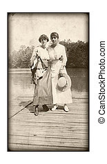 An original vintage photo of two women standing on a dock at the waters edge.