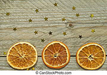 Vintage wooden background with Christmas wreath - dried orange slices and gold confetti in shap of star. Top view with copy space