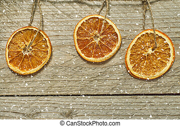 Vintage wooden background with Christmas wreath - dried orange slices hang on rope and falling snow. Greeting card with copy space, Top view