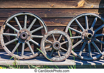 Vintage wooden cart wheels on the background of a wooden wall.