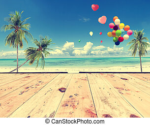 Vintage wooden floor with heart balloon on beach blue sky