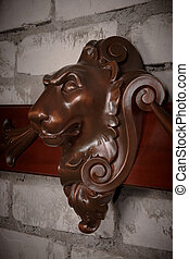 vintage wooden lion head against brick wall
