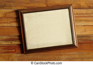 Vintage wooden picture frame on the old wooden wall