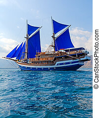 Vintage Wooden Ship with Blue Sails near Komodo Island,...