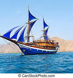Vintage Wooden Ship with Blue Sails near Komodo Island,...