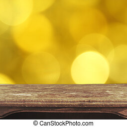 Vintage wooden table with yellow bokeh background