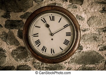 Vintage wooden wall clock on stone wall