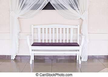 Vintage wooden white violet bench against a white wall with a white curtain and window.