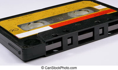Vintage Yellow Audio Cassette Rotates on White Background. Retro tape cassette with a blank label. Old music. Close-up.
