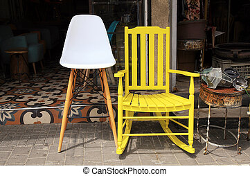 Vintage yellow rocking chair and lamp on street flea market