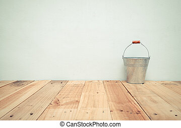 Vintage zinc bucket on wooden table and cement wall background