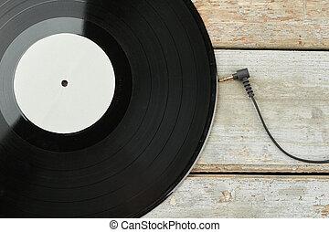 Vinyl LP record on wooden background.