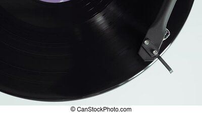 Vinyl record is spinning on a turntable with arm and needle,...