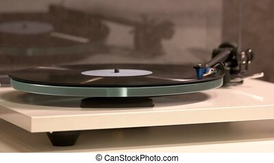 Vinyl record on a turntable record player. The tonearm on a ...