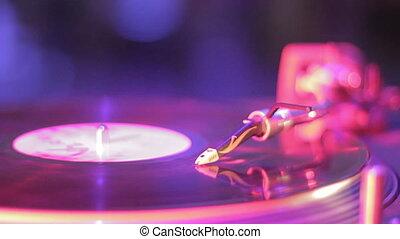 """Vinyl record rotating on sound deck, light flashing in nightclub"""