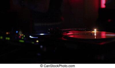 """Vinyl record rotating on turntable, DJ at work, strobe light"""