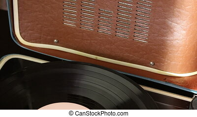 Vinyl record spins on the player. The loudspeaker is...