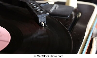 Vinyl record spins on the player. The tracks are visible,...