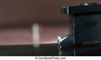 Vinyl record spins on the player. Visible pickup needle. The...