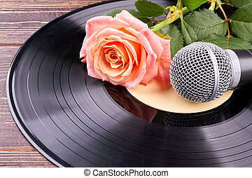 Vinyl record with microphone and rose.