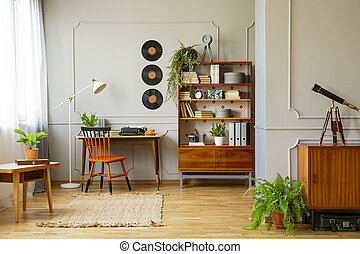 Vinyl records decorations on a gray wall with molding and wooden furniture in a retro home office interior for a writer. Real photo.
