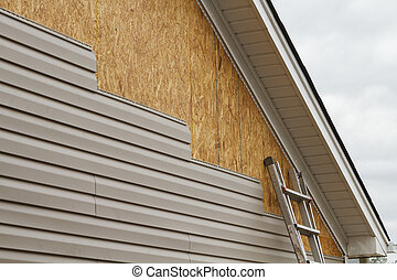 New beige vinyl siding being installed over an osb (oriented strand board) substrate on a residential house in the Southeastern USA region on a cloudy day. The old vinyl siding was being replaced after a hail storm.