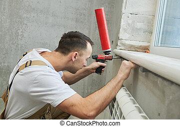 Windowsill installation. Builder worker using polyurethane foam when installing plastic vinyl sill for seal the hole