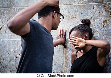 Violent young man threatening his girlfriend with his fist...