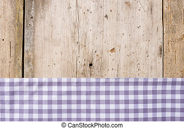 Violet checkered tablecloth on a rustic wooden background