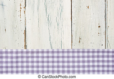 Violet checkered tablecloth on a white wooden background
