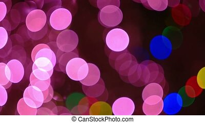 Violet Christmas and New Year Decoration. Abstract Blurred Bokeh Holiday Background. Blinking Garland. Pink Christmas Tree Lights Twinkling Glowing