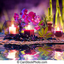 violet composition - candles, oil, orchids and bamboo on...