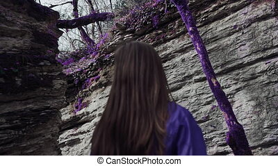 Violet fairytale forest. Girl is slowly walking in a...
