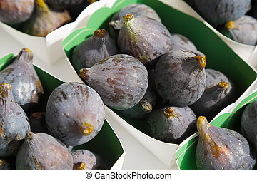 Violet figs in a paper containers are put up for sale on fruit market